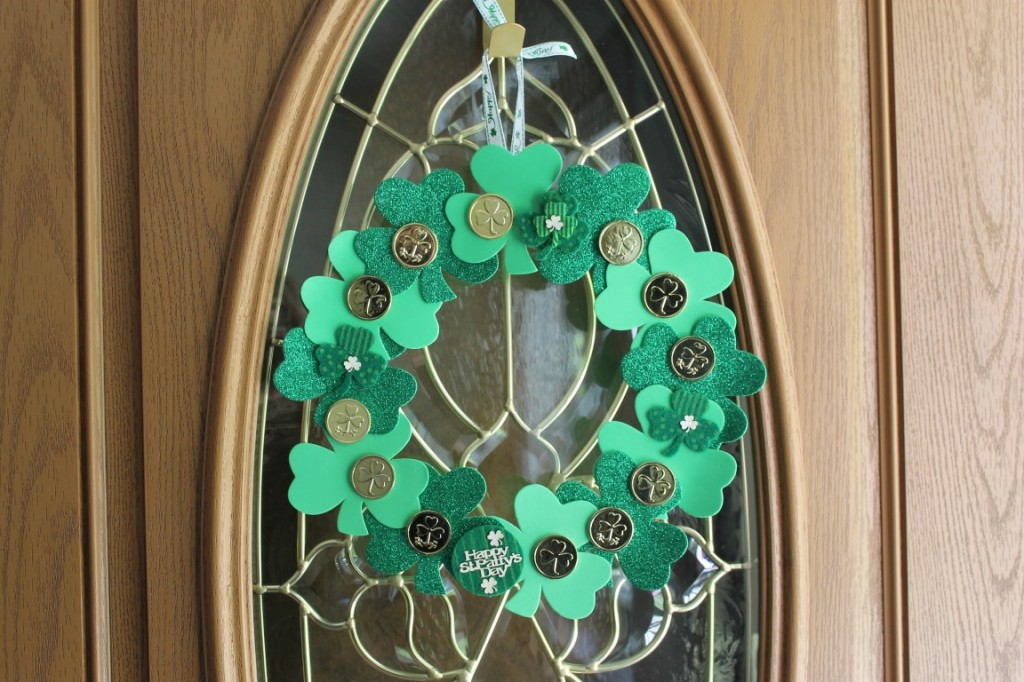 Made from a cardboard wreath form (made from a cereal box) foam shamrocks, gold coin table scatter, felt stickers and ribbon.