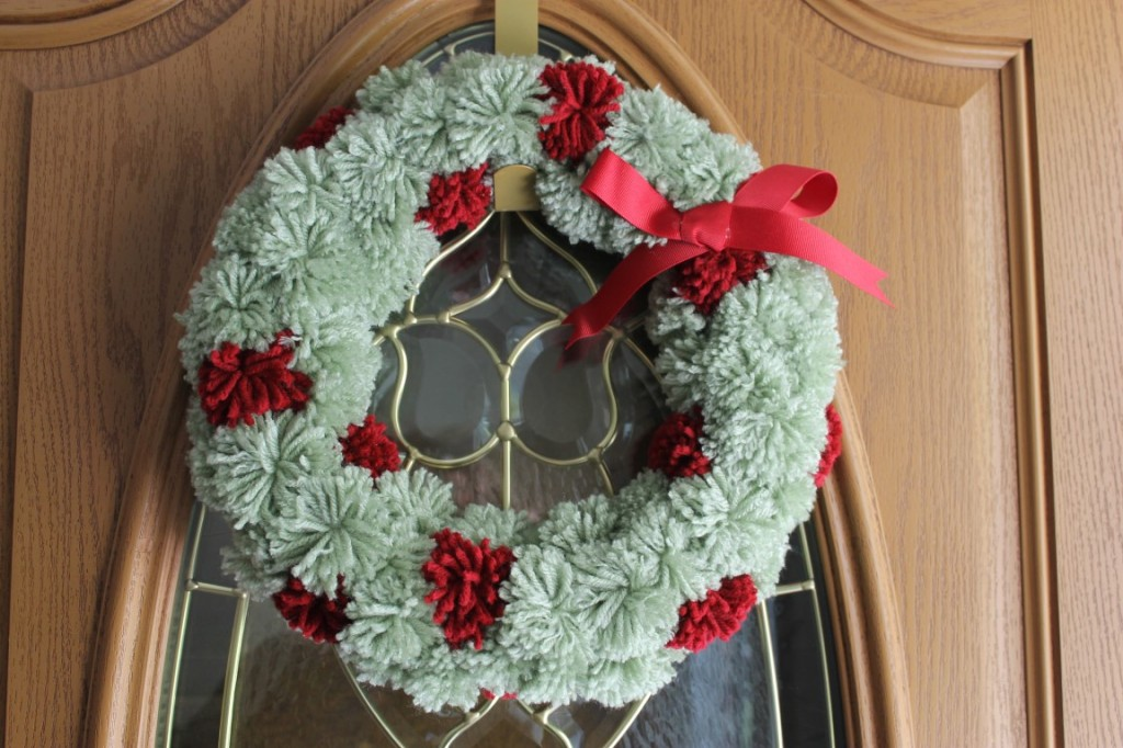 Made from yarn pom-poms, Styrofoam wreath form, ribbon and hot glue.